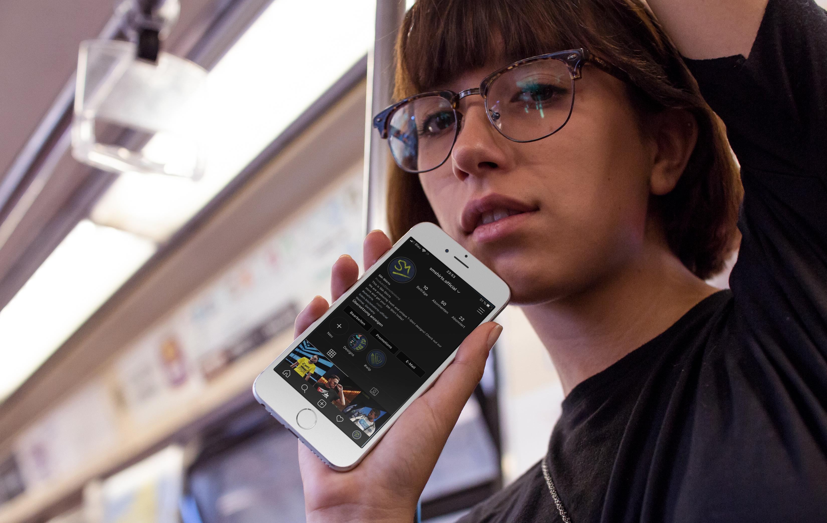 Junge Frau mit einem Smartphone. Es zeigt die Social-Media-Marketing präsenz auf Instagram
